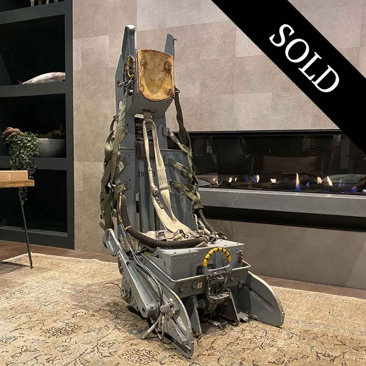 Lockheed Ejection seat in front of fireplace.