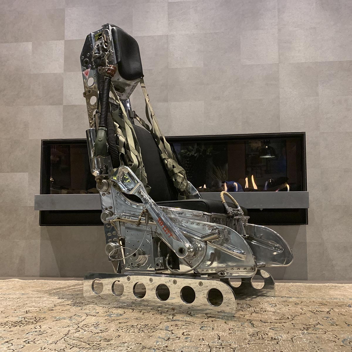 Polished Lockheed Martin ejection seat in front of fireplace.