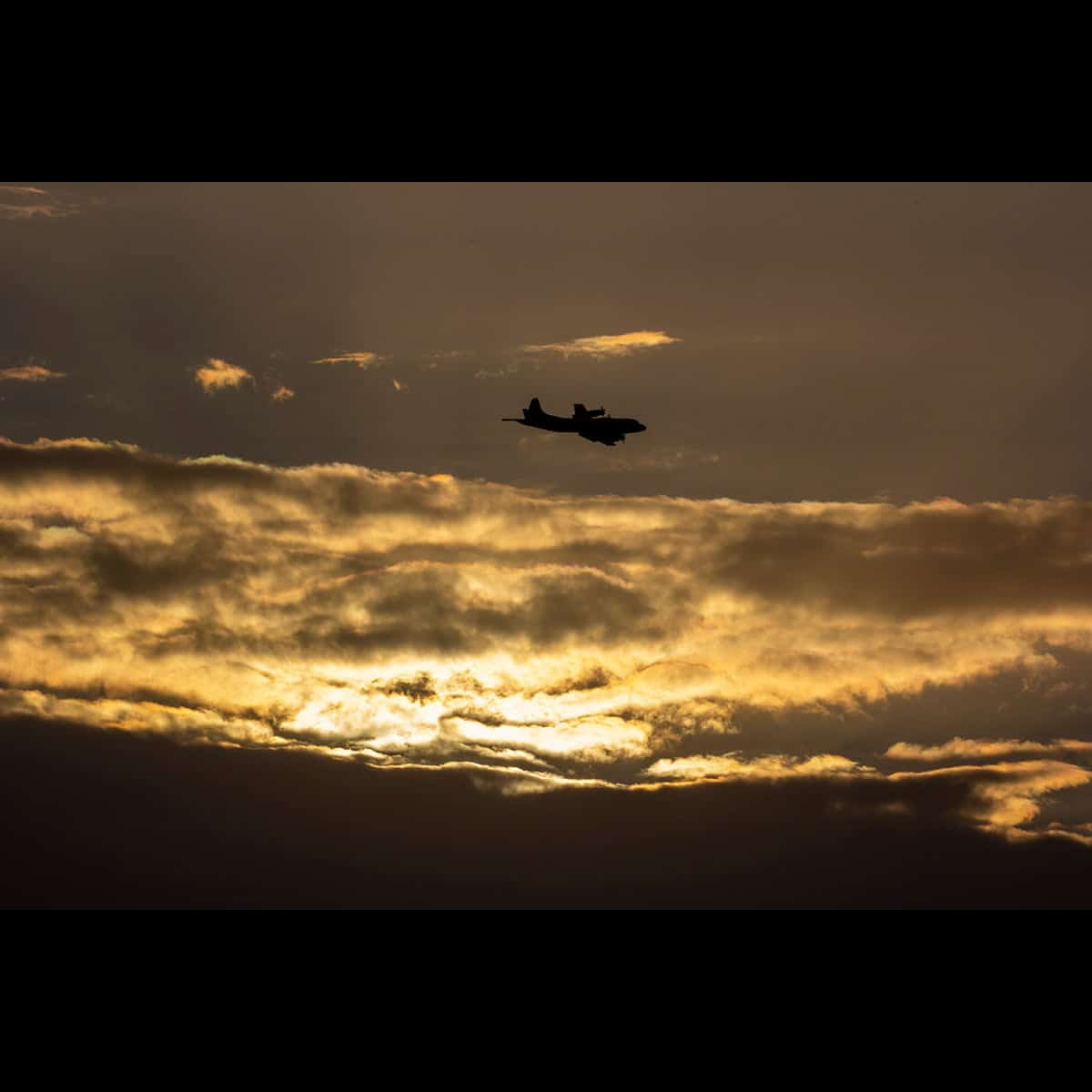 P-3 Orion flying over clouds photo.