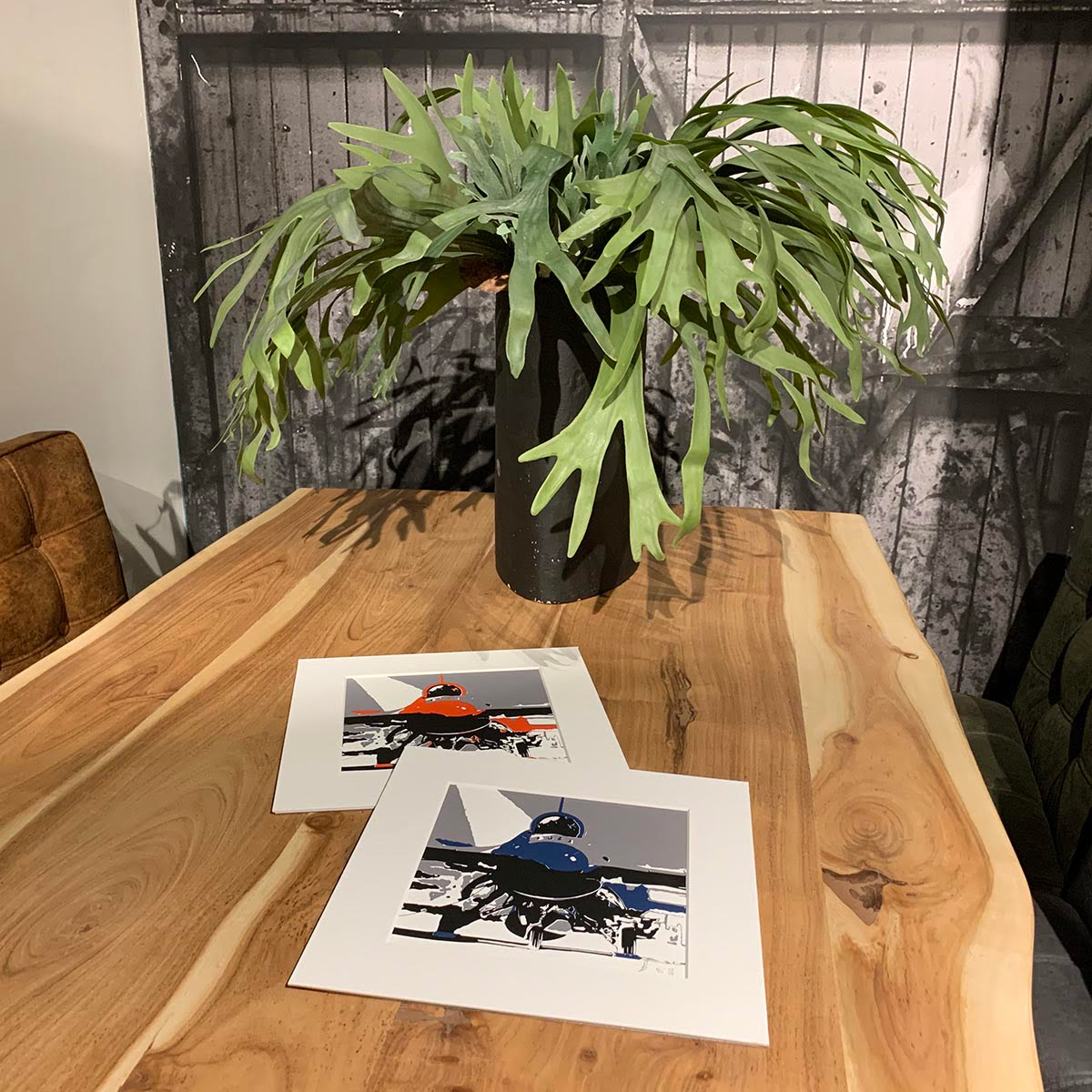 Three colour screen prints, red or blue, black and grey, of a Lockheed Martin F-16 on a dinner table.
