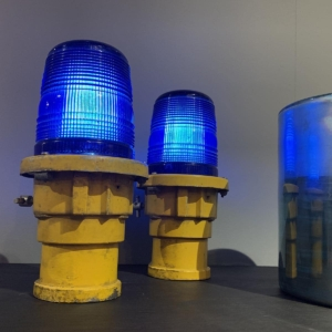 Two blue taxiway lights on a cabinet.