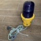 Yellow taxiway light with cord and switch.