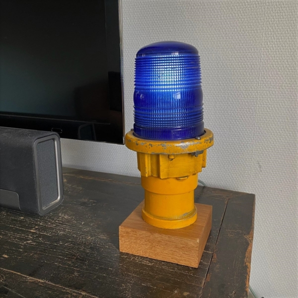 Yellow taxiway light fitted on an oak base.