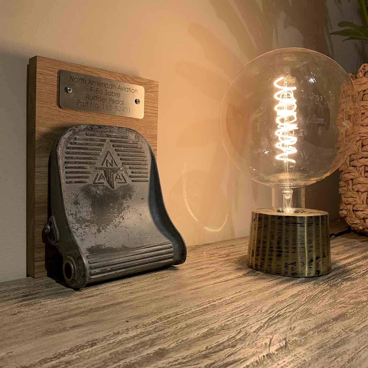 North American F-86 Sabre rudder pedal on a wooden base next to a lamp.