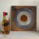 Royal Air Force steel roundel artwork next to some bottles on a shelf.