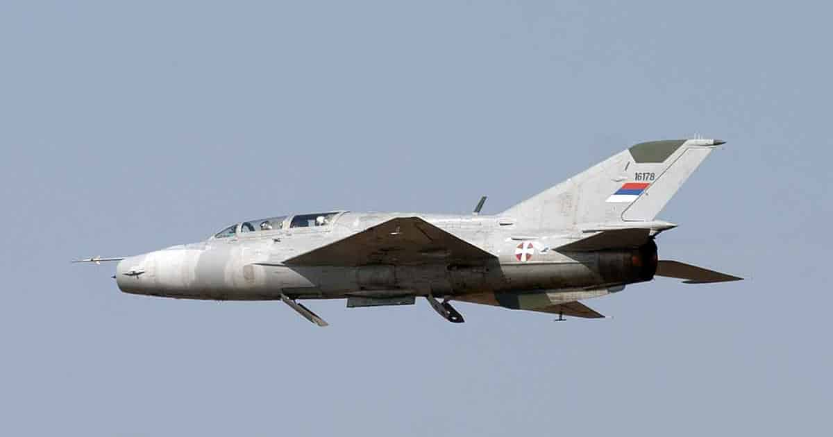 Mikoyan-Gurevich MiG-21UM in flight showing the extended speed brakes.